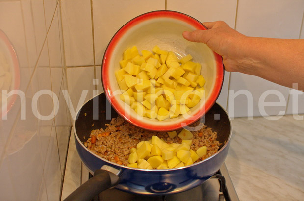 Мусака с кайма и броколи - изсипване на картофите