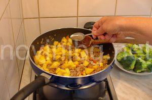 Мусака с кайма и броколи - поръсване с подправки